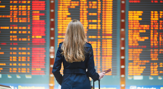 Flight delay compensation, woman stood in front of airport departures board showing delays and cancellations